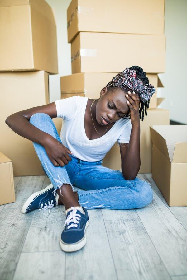 Mulher africana triste ilimitada feliz devido a mover a casa nova de seu sonho, sentando-se no assoalho com lotes de caixas de ca imagens de stock royalty free