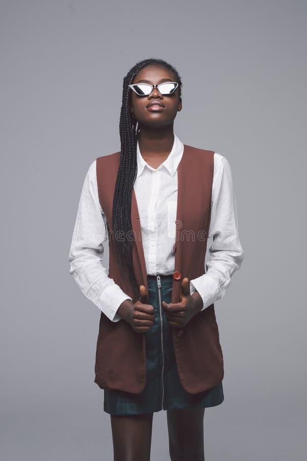 Mulher afro-americana bonita nova que levanta em óculos de sol elegantes e em roupa isolados no fundo cinzento fotos de stock royalty free