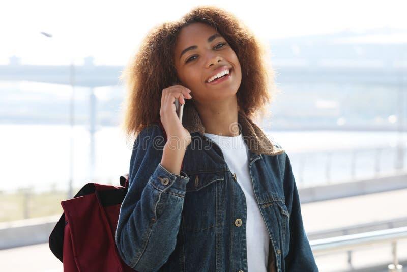Mulher afro-americana bonita que usa o móbil na rua Conceito de uma comunicação e do estilo de vida imagens de stock royalty free