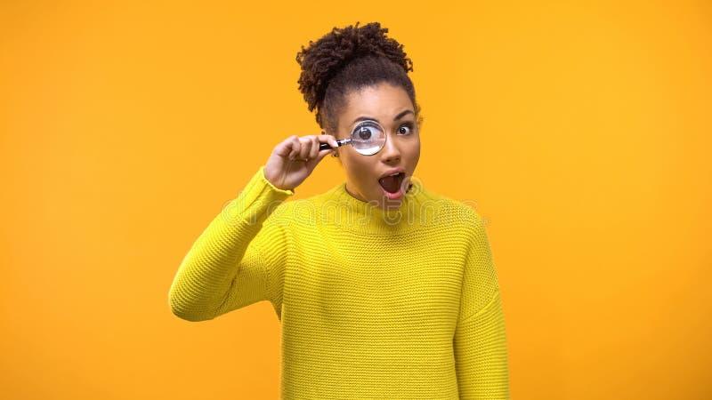 Mulher afro-americana curiosa que olha a lupa, tendo o divertimento, surpresa fotografia de stock royalty free