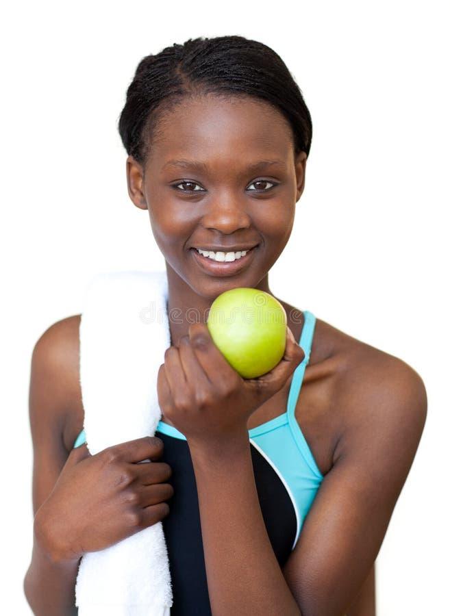 Mulher afro-americana da aptidão que come uma maçã fotografia de stock