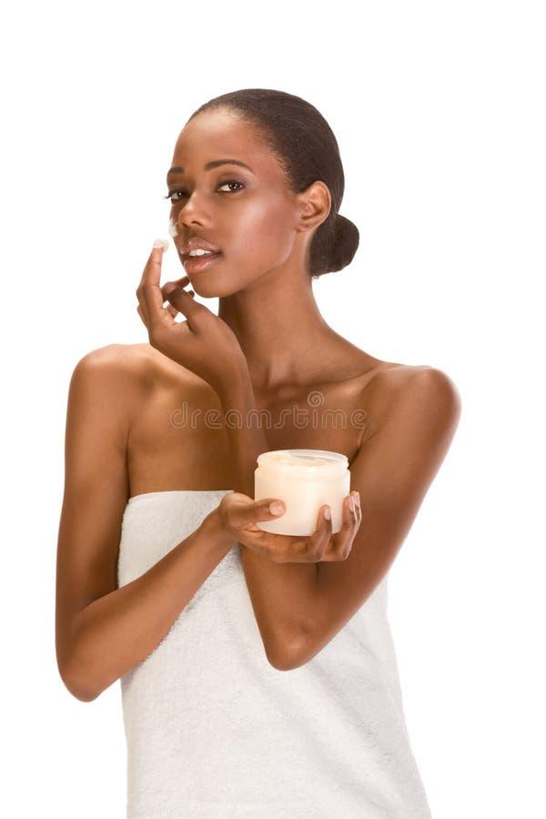A mulher afro-americana na toalha põr o creme sobre a face imagens de stock