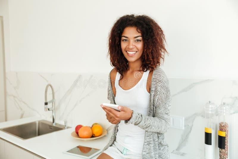 Mulher afro-americana nova alegre que usa o telefone celular foto de stock royalty free