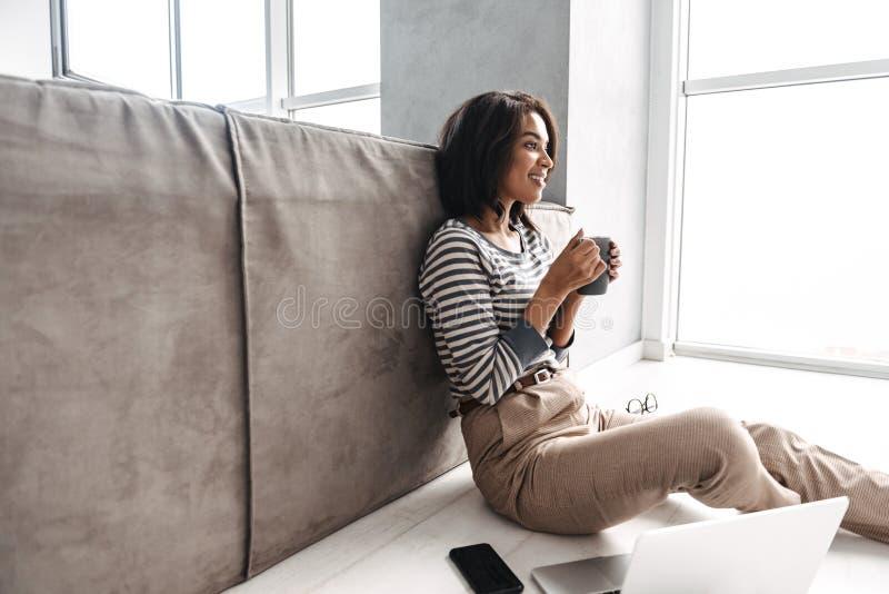 Mulher afro-americana nova atrativa que senta-se em um sofá foto de stock