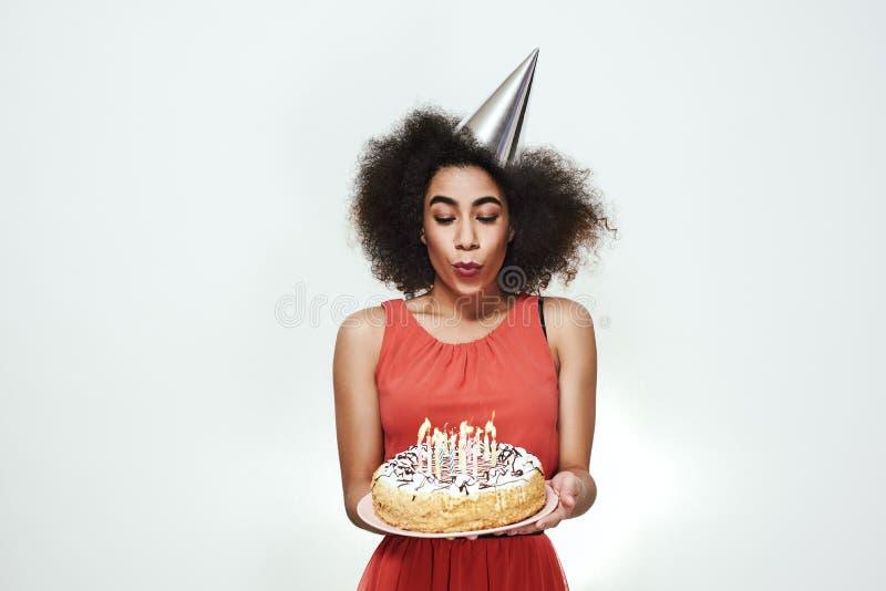 A mulher afro-americana nova bonita no chapéu de prata do partido está comemorando seu aniversário e está fundindo para fora as v fotografia de stock royalty free