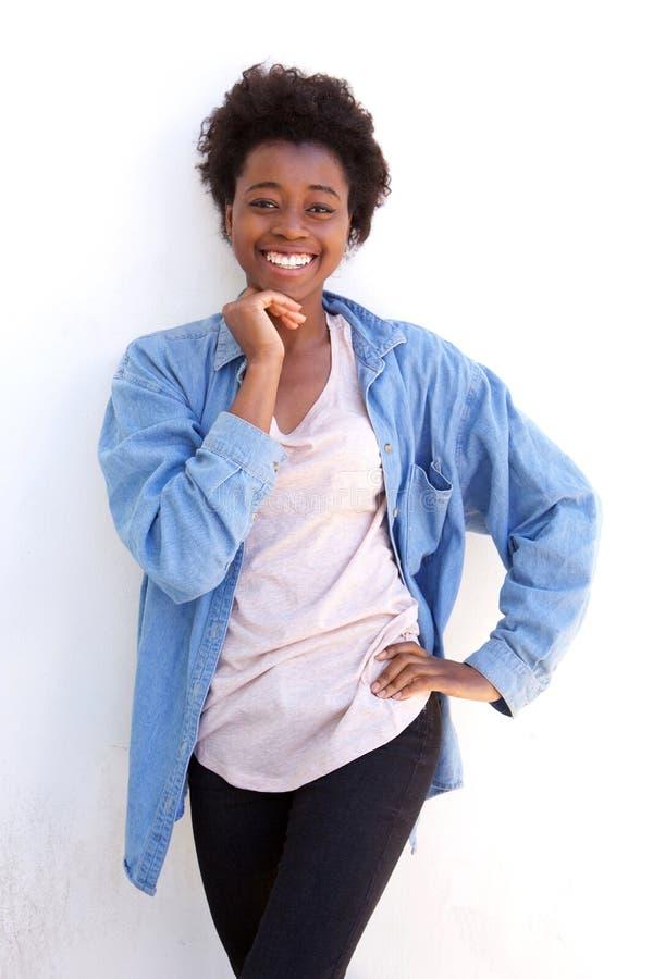 Mulher afro-americana nova bonito com mão no queixo e posição contra a parede branca fotos de stock royalty free