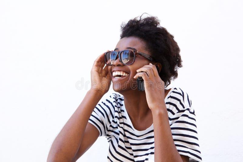 Mulher afro-americana nova de riso com telefone celular foto de stock royalty free