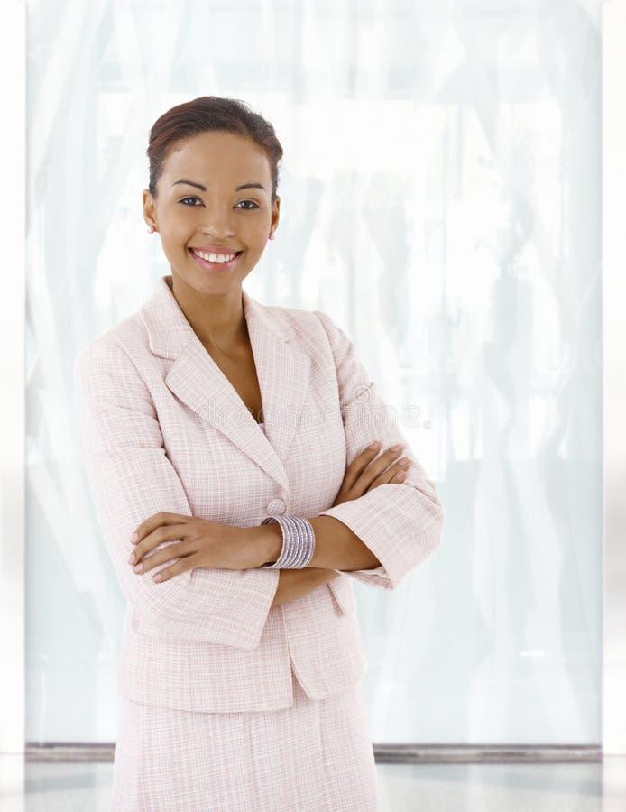 Mulher afro-americana nova feliz na entrada do escritório fotos de stock
