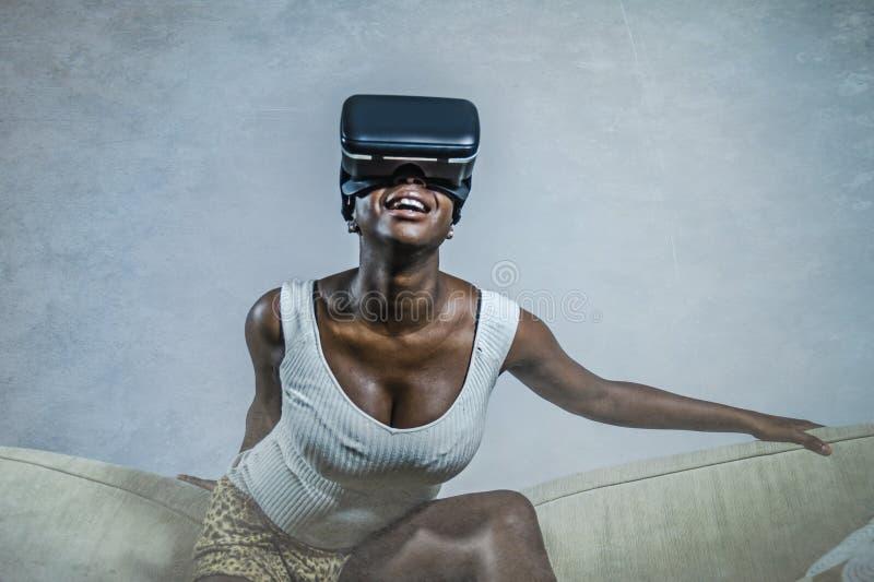Mulher afro-americana preta atrativa nova que joga os auriculares dos óculos de proteção de VR que tentam tocar na ilusão no sofá fotografia de stock royalty free