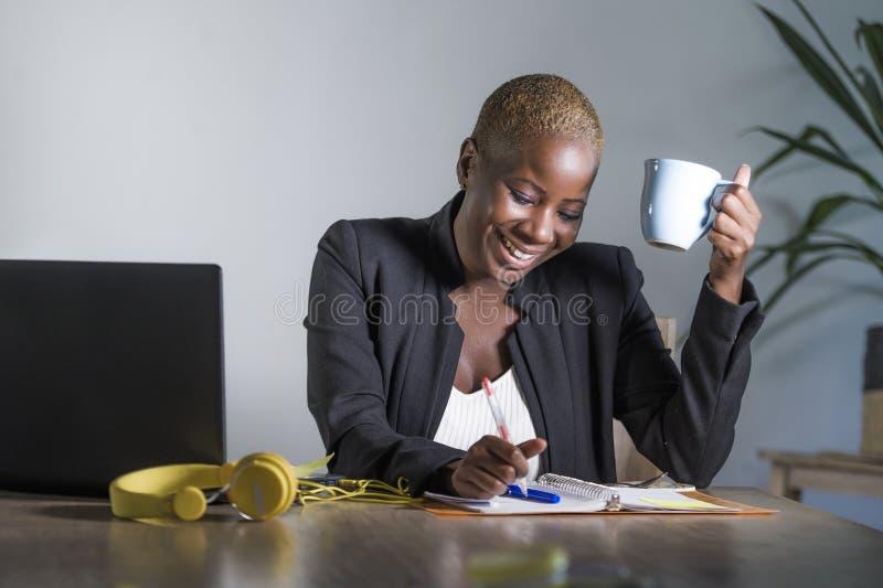Mulher afro-americana preta bem sucedida atrativa e feliz nova no trabalho do revestimento do negócio alegre no portátil do escri fotografia de stock royalty free