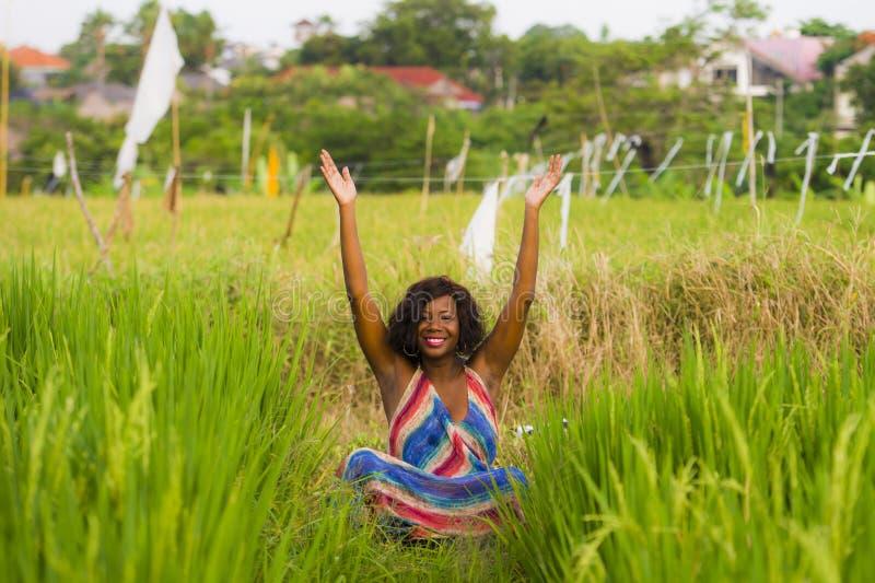 A mulher afro-americana preta bonita e feliz nova que senta-se em rive o campo que pratica fora o abrandamento e a meditação da i imagem de stock