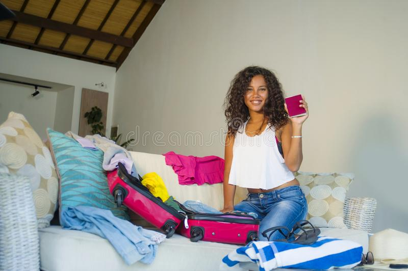 A mulher afro-americana preta feliz atrativa e louca nova que prepara a roupa que embala o material na mala de viagem que sae por fotografia de stock royalty free