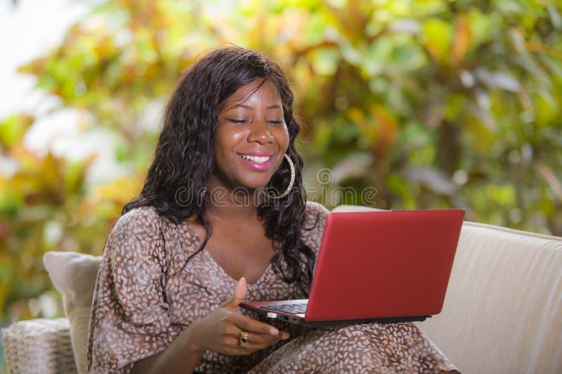 Mulher afro-americana preta feliz e bonita nova no vestido elegante e trabalho com a apreciação do laptop autônomo fotografia de stock royalty free
