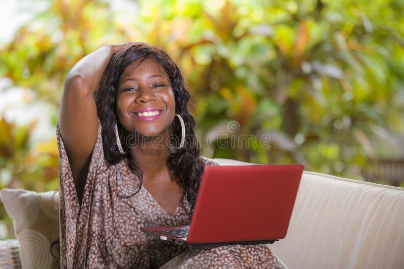 Mulher afro-americana preta feliz e bonita nova no vestido elegante e trabalho com a apreciação do laptop autônomo fotografia de stock