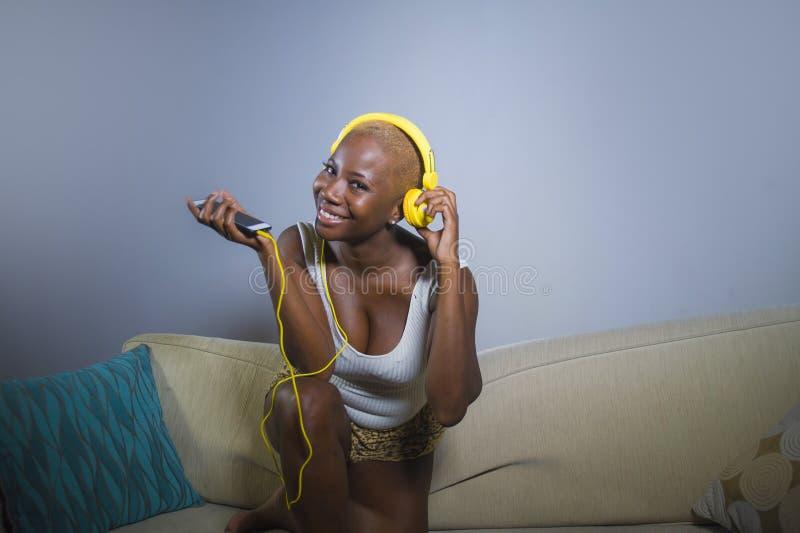 Mulher afro-americana preta relaxado feliz e bonita nova que escuta a música com fones de ouvido e sofá do sofá do telefone celul imagens de stock royalty free