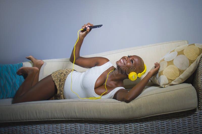 Mulher afro-americana preta relaxado feliz e bonita nova que escuta a música com fones de ouvido e sofá do sofá do telefone celul fotografia de stock royalty free