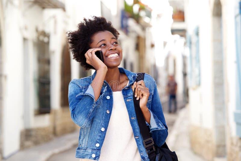Mulher afro-americana que fala no telefone celular e que sorri fora fotos de stock