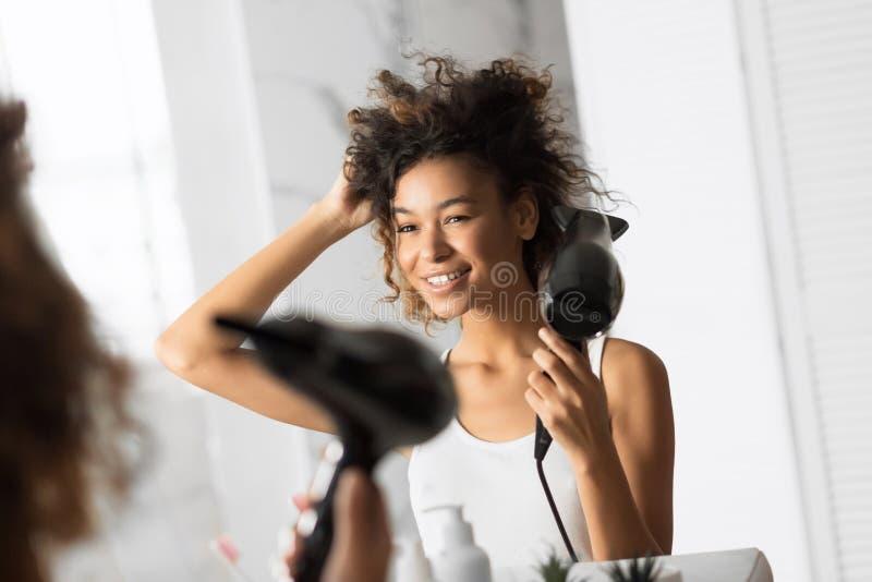 Mulher Afro-Americana Secando Cabelo Com Ventilador Em Banheiro fotos de stock royalty free