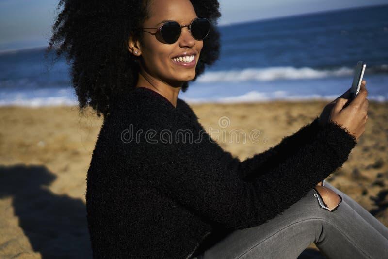 A mulher afro-americano alegre encantador que envia multimédios arquiva dos trópicos através do smartphone e da conexão sem fio foto de stock royalty free