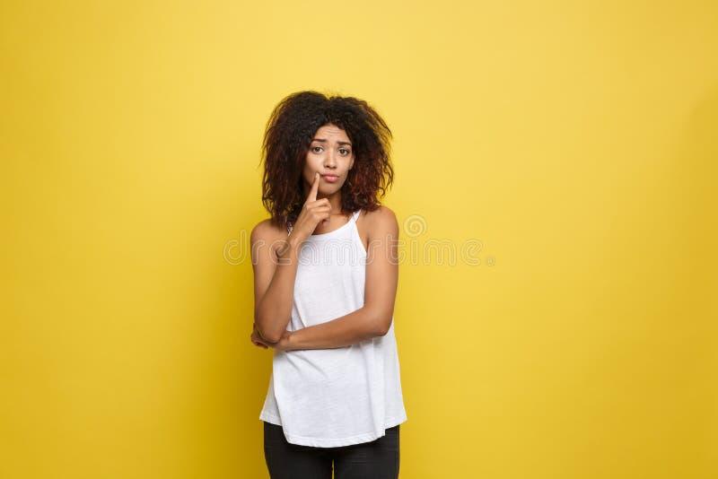 Mulher afro-americano atrativa bonita com cabelo afro encaracolado que pensa de algo Fundo amarelo do estúdio cópia fotos de stock royalty free