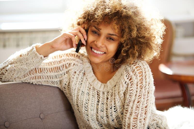 Mulher afro-americano atrativa que relaxa em casa e que fala no telefone celular imagem de stock royalty free