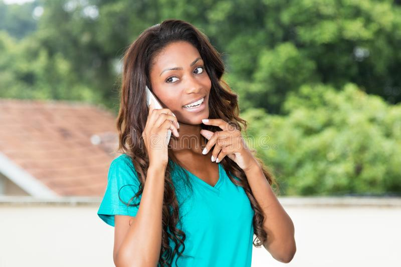 Mulher afro-americano bonita com cabelo longo no telefone celular imagens de stock