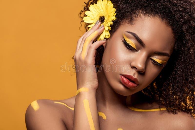 Mulher afro-americano bonita com composição artística e gerbera no sonho do cabelo fotos de stock