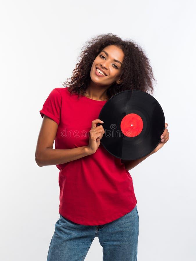 Mulher afro-americano bonita nova no t-shirt vermelho que aprecia e que dança com registro de vinil no fundo branco Retrato fotografia de stock royalty free