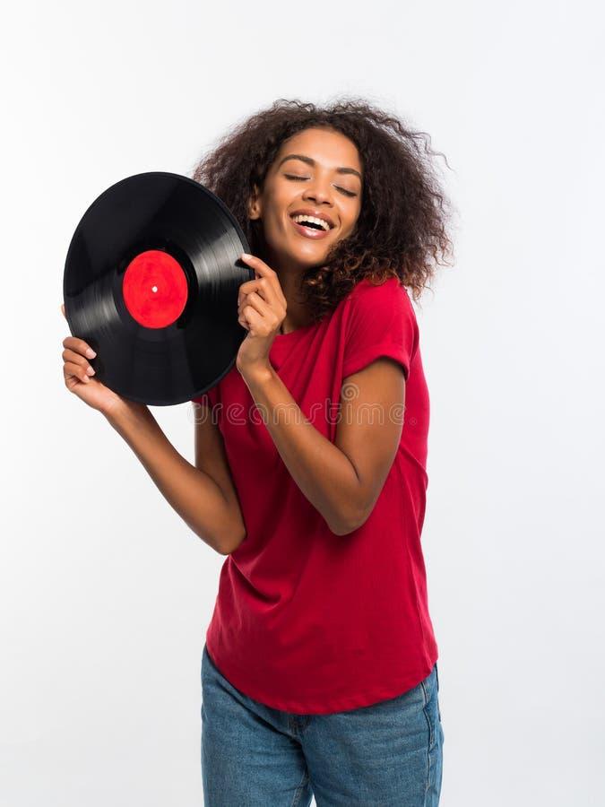 Mulher afro-americano bonita nova no t-shirt vermelho que aprecia e que dança com registro de vinil no fundo branco Retrato fotos de stock royalty free
