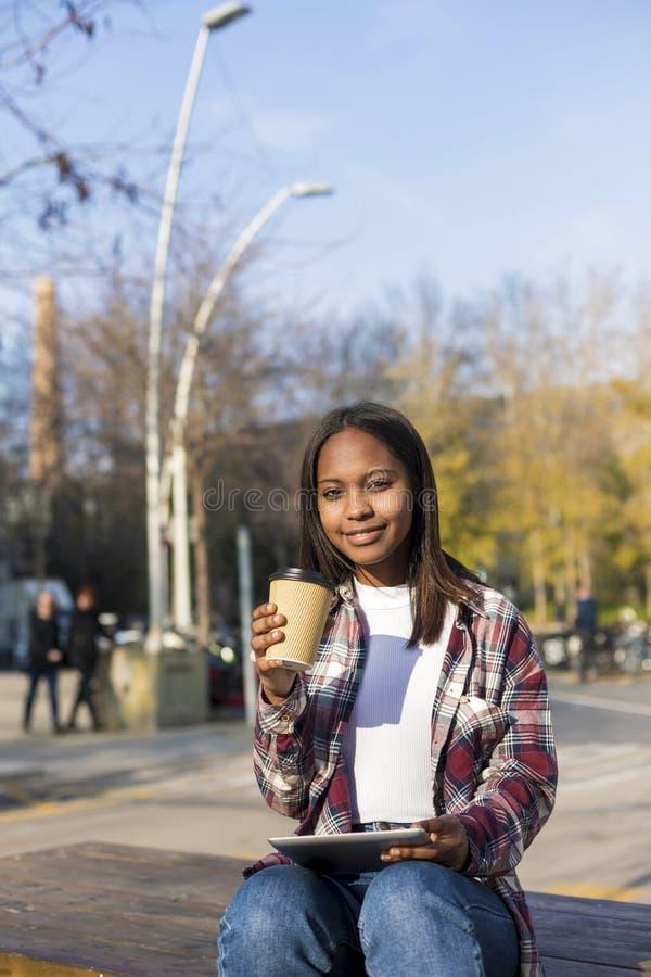 Mulher afro-americano bonita nova que senta-se fora na cidade com um PC da tabuleta ao guardar para levar embora o café em um ens fotos de stock royalty free