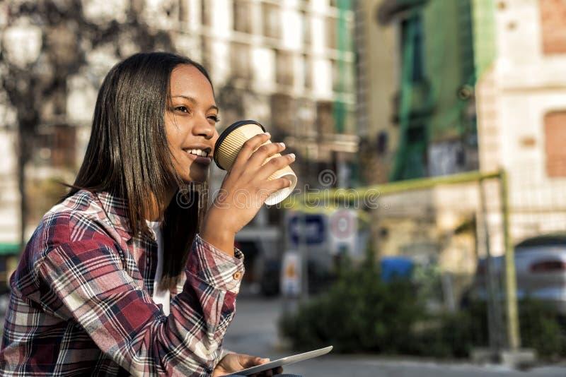 Mulher afro-americano bonita nova que senta-se fora na cidade com um PC da tabuleta ao guardar para levar embora o café em um ens foto de stock royalty free