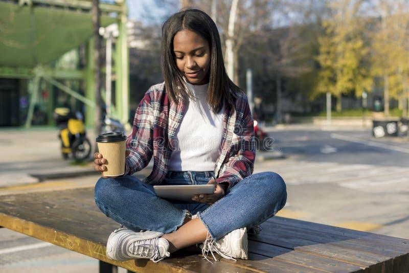 Mulher afro-americano bonita nova que senta-se fora na cidade com um PC da tabuleta ao guardar para levar embora o café em um ens imagens de stock royalty free