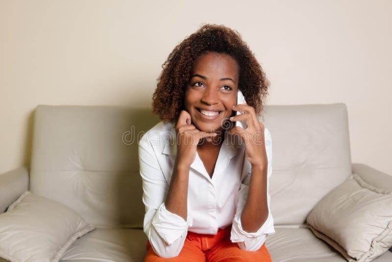 Mulher afro-americano bonita que ri do telefone no sofá foto de stock