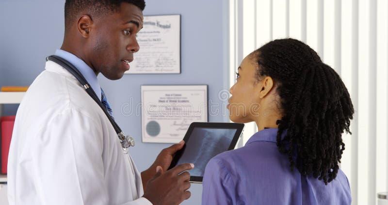 Mulher afro-americano com dor de pescoço que fala ao doutor imagens de stock