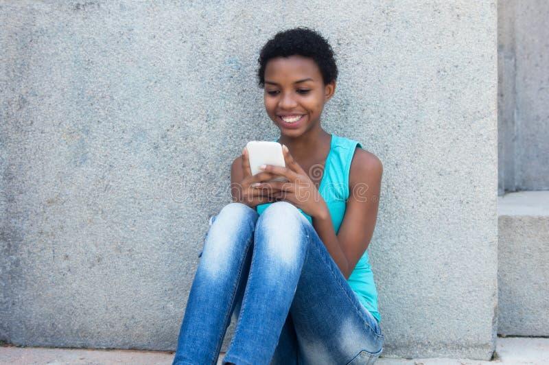 Mulher afro-americano com o cabelo curto que envia a mensagem com phon foto de stock