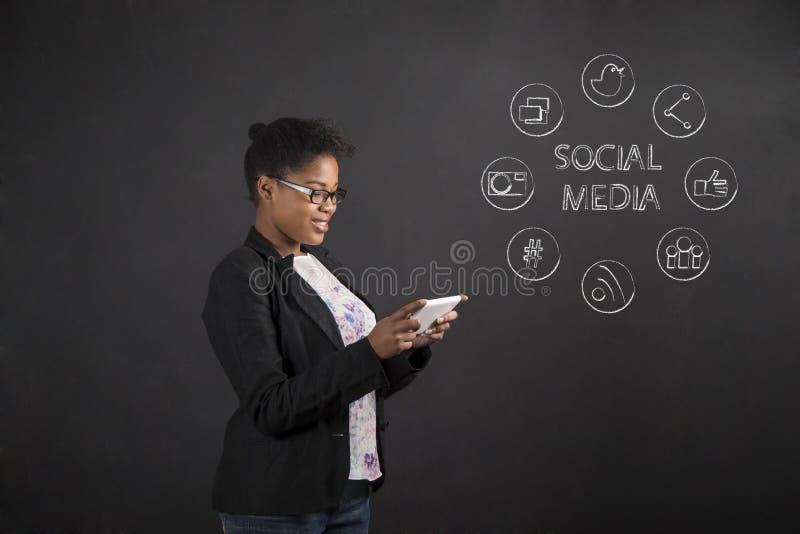 Mulher afro-americano com trabalhos em rede sociais da tabuleta no fundo do quadro-negro imagens de stock royalty free