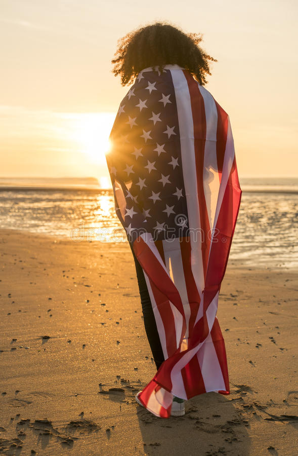 Mulher afro-americano da menina da raça misturada envolvida na praia da bandeira dos E.U. fotografia de stock
