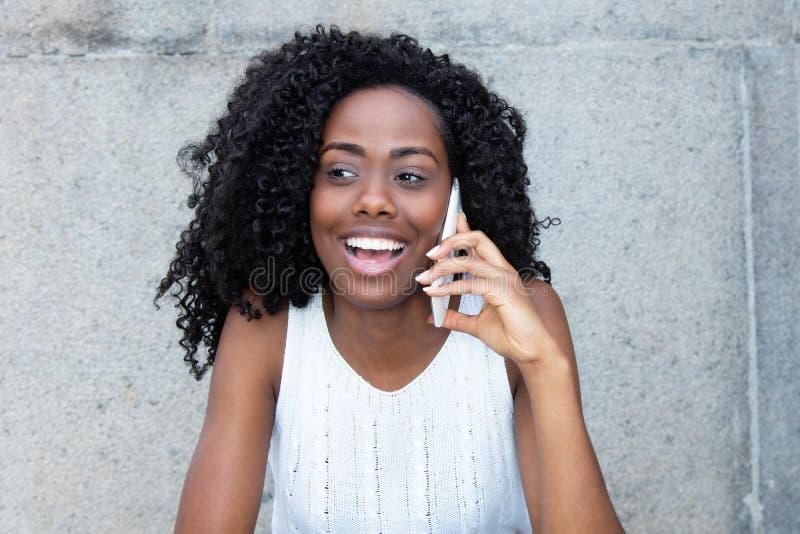 Mulher afro-americano de riso no telefone celular fotografia de stock royalty free