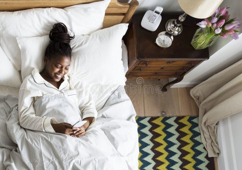 Mulher afro-americano de sorriso na cama usando um telefone celular imagens de stock