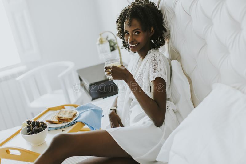 A mulher afro-americano de sorriso que come um café da manhã de relaxamento em seja foto de stock royalty free