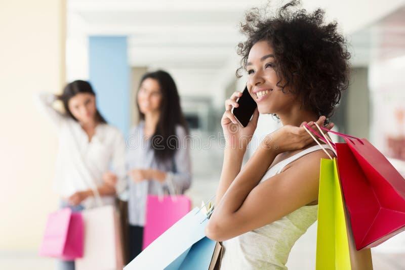 Mulher afro-americano entusiasmado que fala no telefone celular na alameda foto de stock royalty free