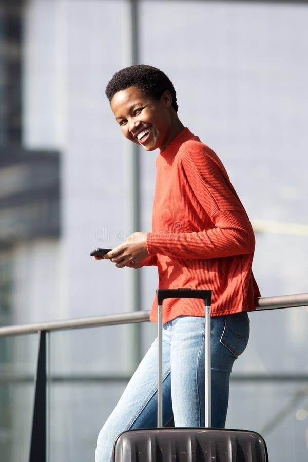 Mulher afro-americano feliz do curso que espera na estação com telefone celular e mala de viagem imagem de stock royalty free