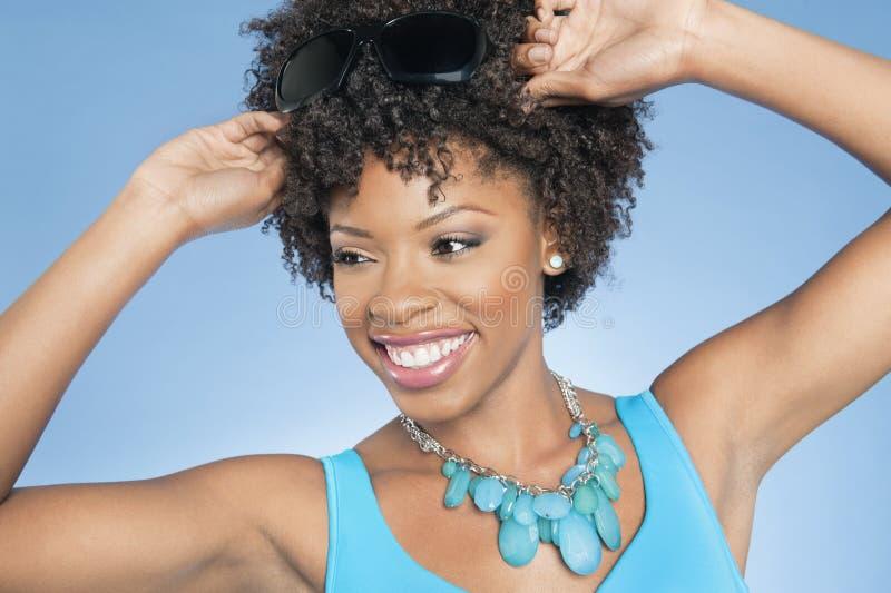 Mulher afro-americano feliz que ajusta óculos de sol ao olhar afastado sobre o fundo colorido imagem de stock