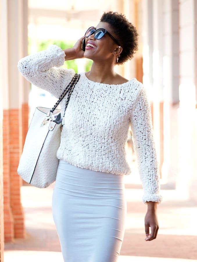 Mulher afro-americano feliz que anda com telefone celular foto de stock royalty free