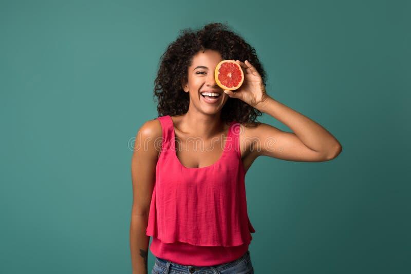 Mulher afro-americano feliz que guarda a metade da toranja foto de stock