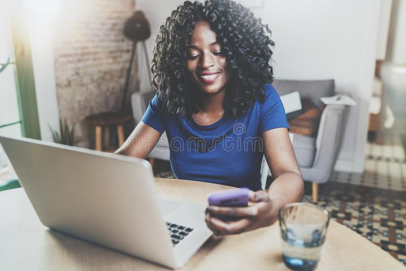 Mulher afro-americano feliz que usa o portátil e o smartphone ao sentar-se na tabela de madeira na sala de visitas horizontal imagem de stock royalty free