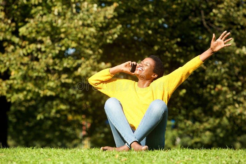 Mulher afro-americano feliz witting no parque e na fala no telefone celular fotografia de stock