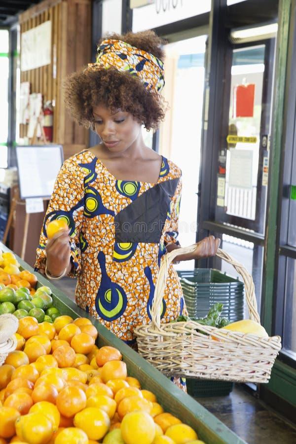 Mulher afro-americano na compra tradicional do desgaste para frutos no supermercado imagens de stock royalty free