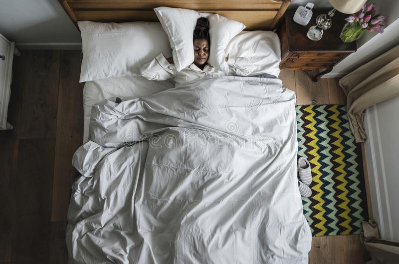 Mulher afro-americano na insônia da cama e no conceito da poluição de ruído imagens de stock royalty free