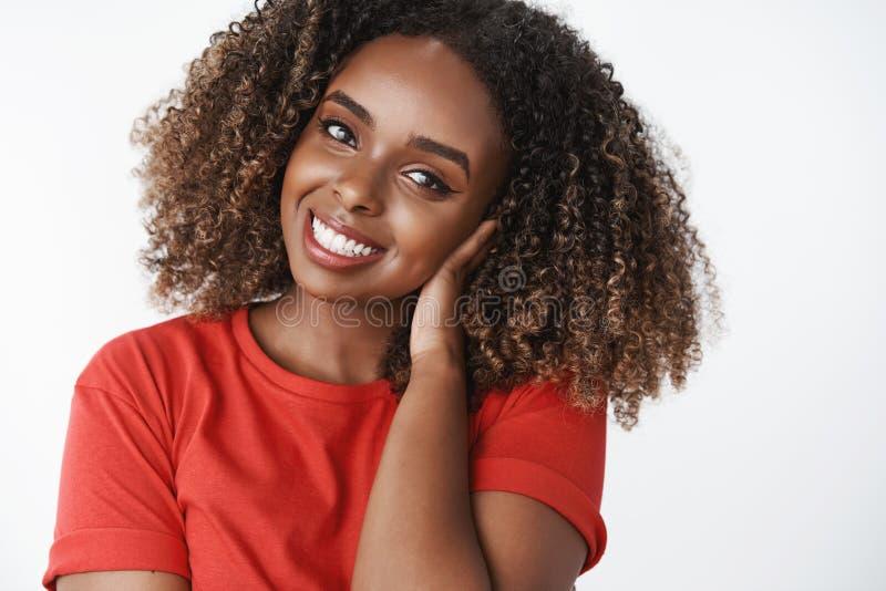 Mulher afro-americano nova atrativa devista macia com o penteado afro encaracolado que penteia o cabelo com mão delicadamente foto de stock royalty free